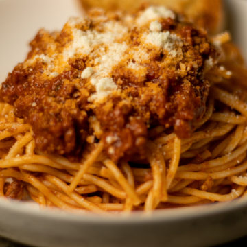 Spaghetti in a bowl topped with grated cheese