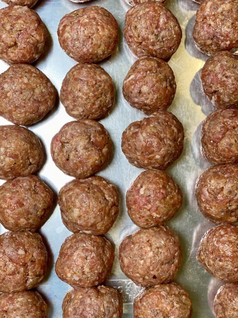 Raw meatballs on an aluminum cookie sheet.