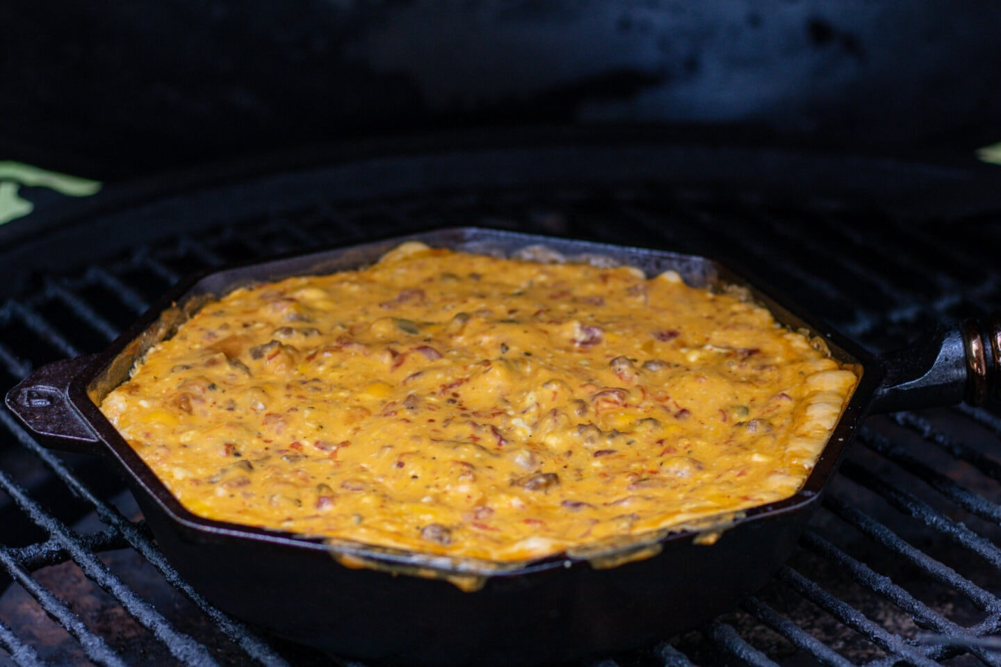 A skillet with melted cheese dip on the grill. The cheese dip is orange and slightly spilling over the edge. It is elected with bits of tomato and sausage.