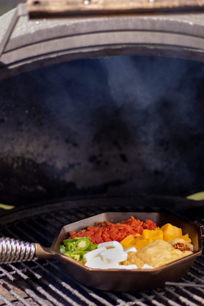 A skillet with tomatoes, cream cheese, velveeta, jalapeños, cream of chicken soup, garlic, and red pepper flakes on a grill with a small trail of smoke