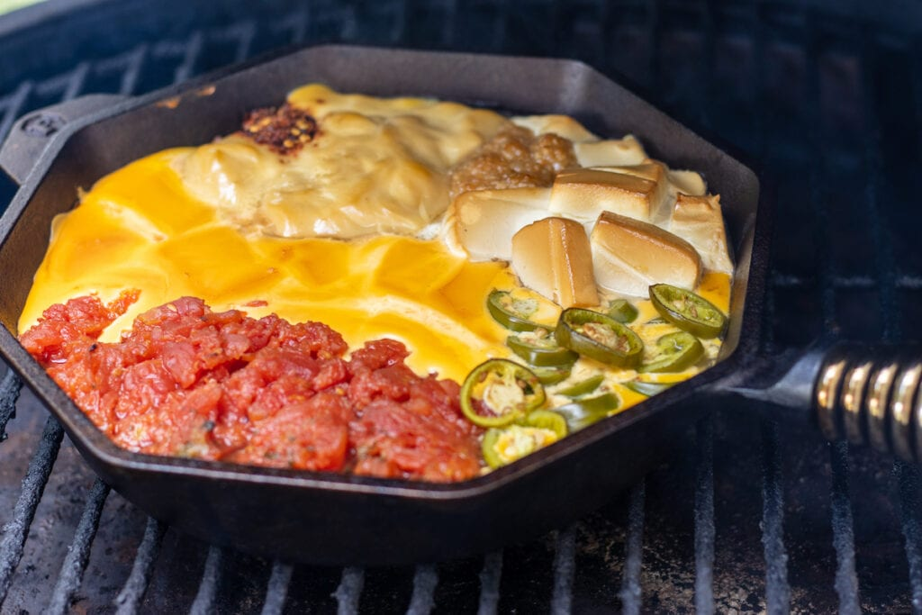 A skillet with tomatoes, cream cheese, velveeta, jalapeños, cream of chicken soup, garlic, and red pepper flakes on a grill smoked a slightly melted.