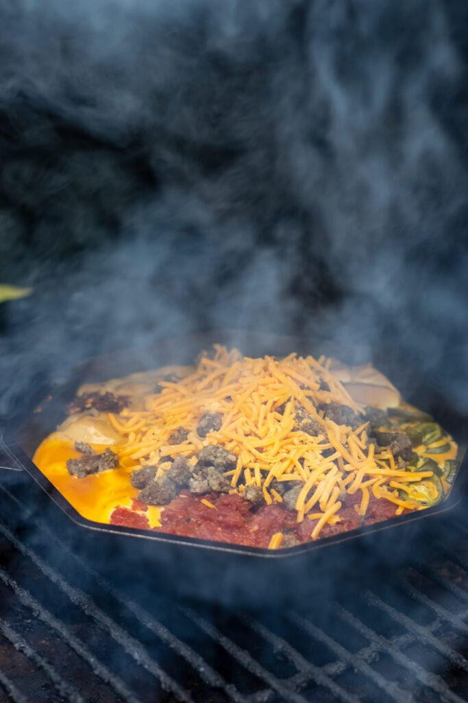 A skillet with tomatoes, cream cheese, velveeta, jalapeños, cream of chicken soup, garlic, and red pepper flakes on a grill  topped with shredded cheddar and crumbled sausage surrounded by smoke