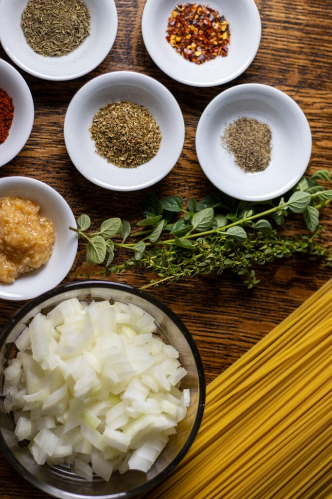 Dried spices, herbs, and garlic in small white bowls, a larger bowl of diced onion is on the bottom left, dried spaghetti is on the bottom right and a bundle of fresh thyme and oregano are in the middle.