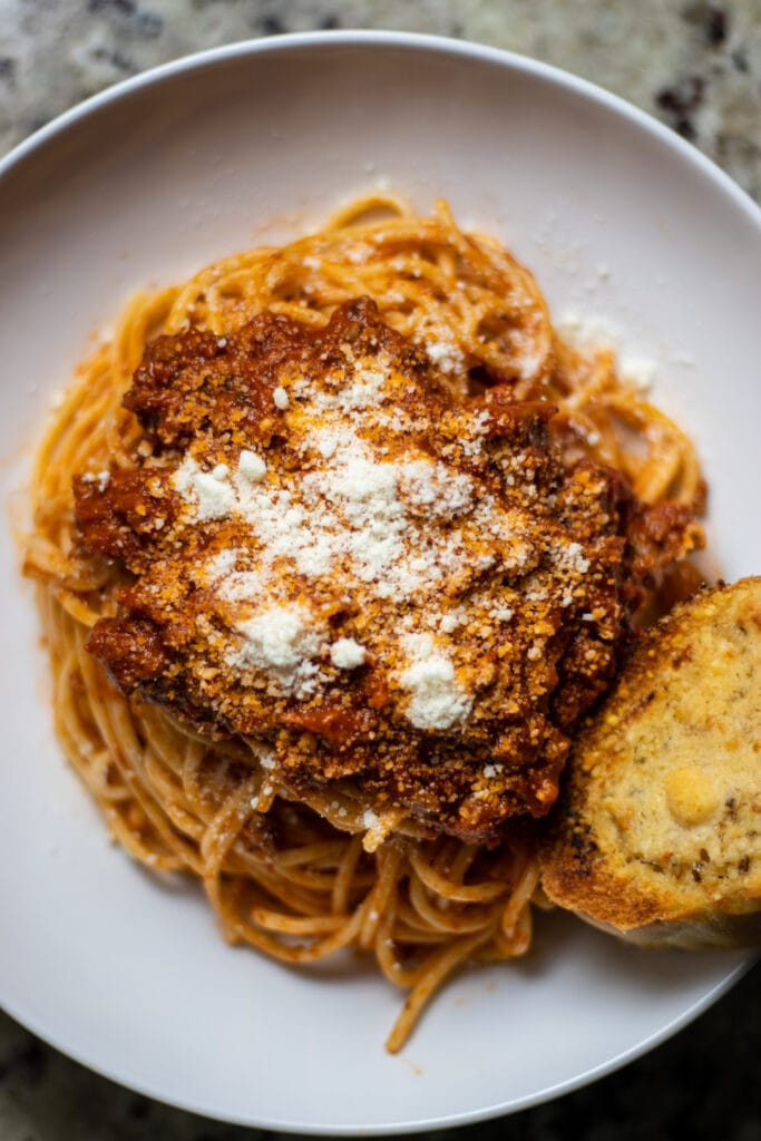 Spaghetti topped with a red marinara sprinkled with grated Parmesan cheese. A piece of garlic bread is on the bottom right.