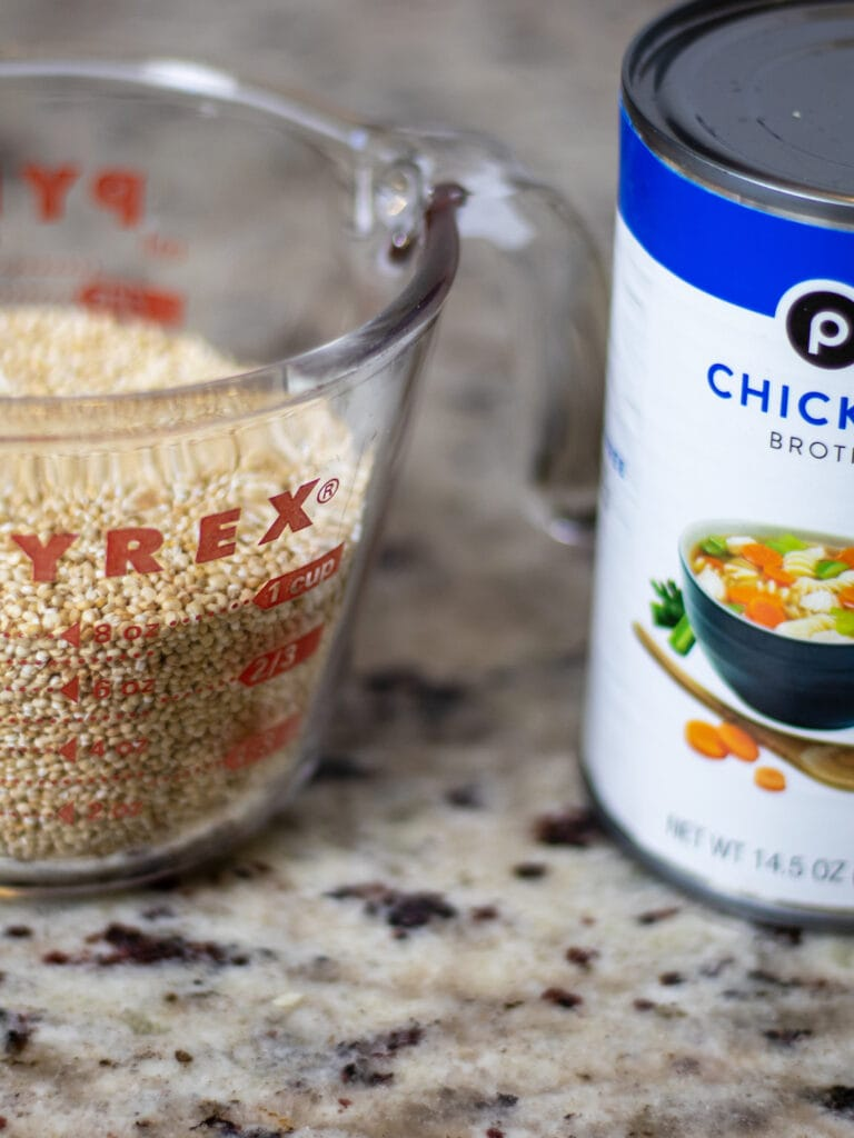 A pyrex measuring cup with dried quinoa on the left and a public can of chicken broth half off frame to the right.