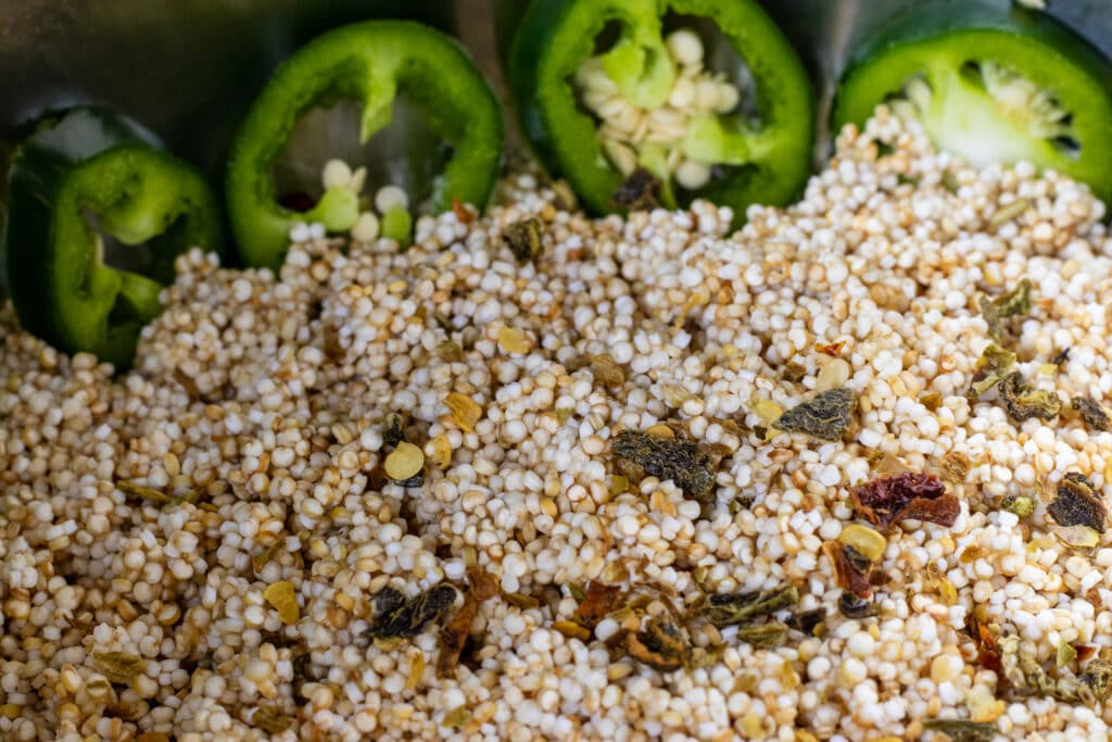 Close up of quinoa in a pot with chicken stock. Dried green peppers are on top and sliced jalapeño peppers line the pot int he background.