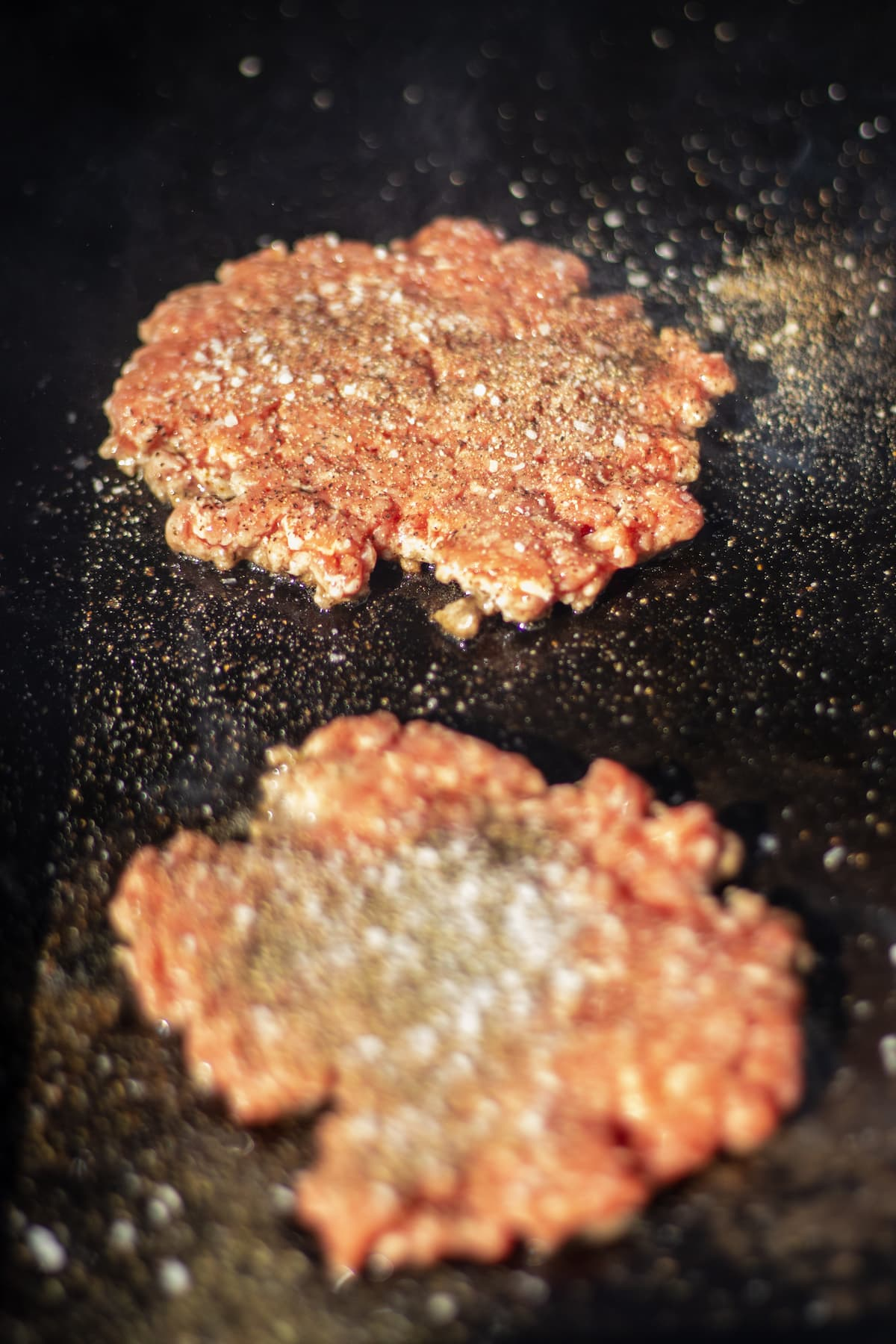 Burger patties that have been pressed on a griddle and seasoned with salt and pepper