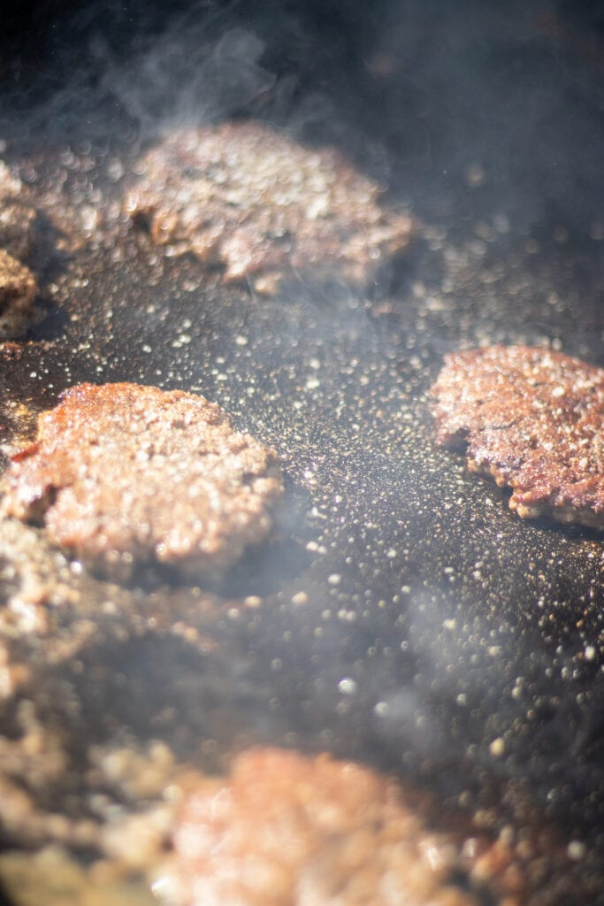 burgers cooking on a griddle
