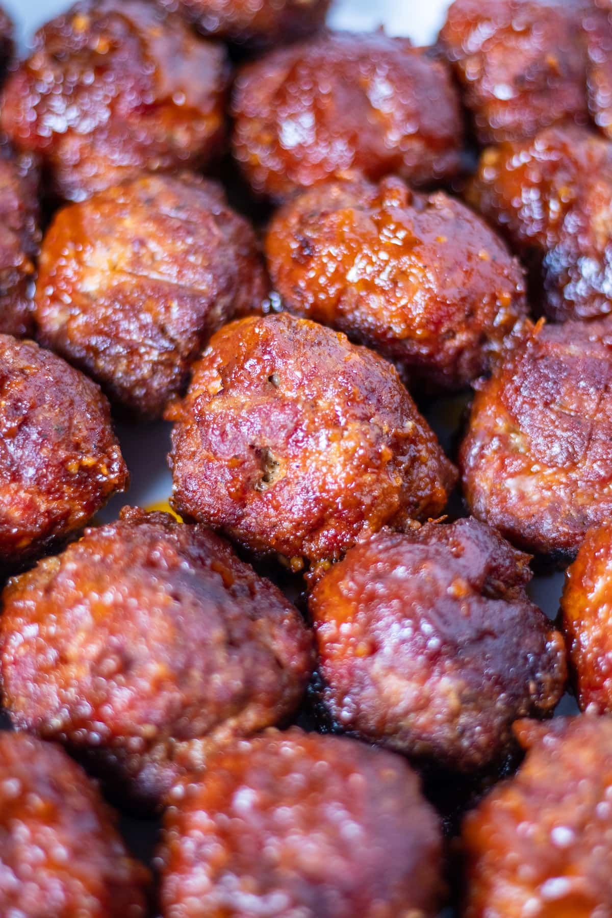 brilliantly red meatballs covered with sticky bbq sauce