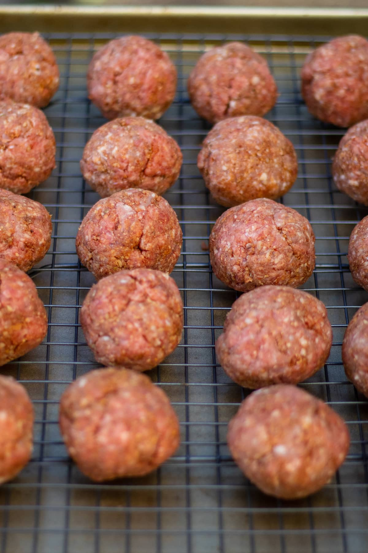raw meatballs resting on a wire rack