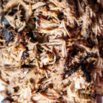 Close up of pulled pork on the big green egg with bark mixed in.