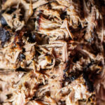 pulled pork close up with bark on a platter.