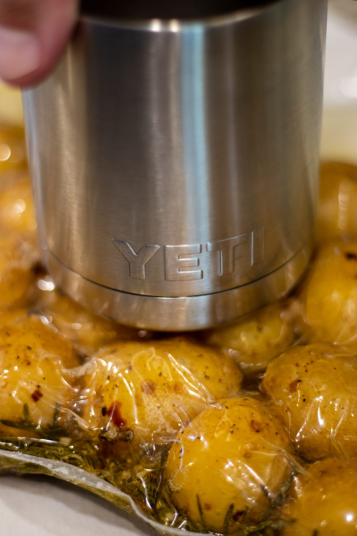 Yukon gold potatoes in a bag being smashed by a yeti tumbler.